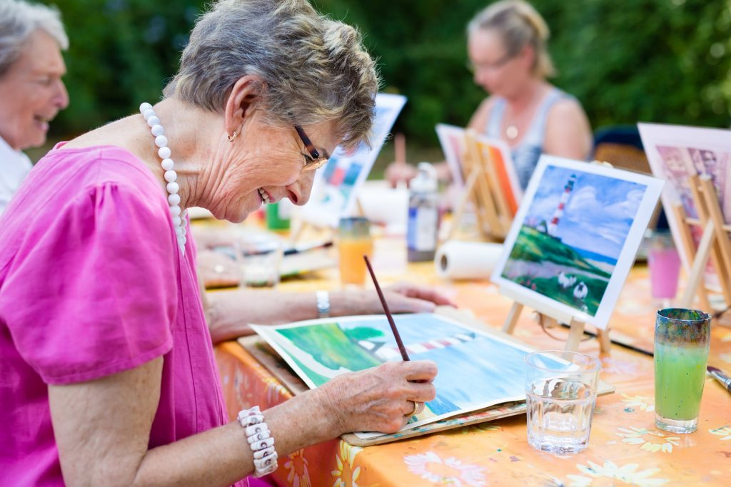 Senior woman smiling while drawing with the group.